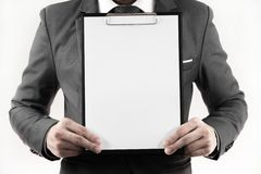 Business man in suit holding a blank clipboard. Isolated on white Stock Images