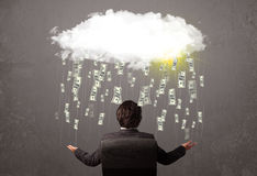 Business man in suit looking at cloud with falling money Royalty Free Stock Images