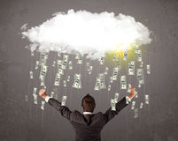 Business man in suit looking at cloud with falling money royalty free stock image