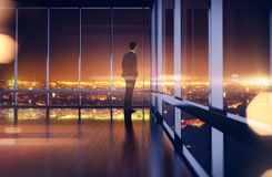 Business man in suit looking at the night city. 3d