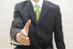 Business man in suit offers to shake hands stock images