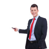 Business man in a suit pointing with a pen. Handsome young business man in a suit pointing with a pen on white background Stock Photos