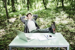 Business man in suit relax at his working office desk in green park with hands over head and legs on table. Great job done. Busine. Business man in suit relax at royalty free stock image
