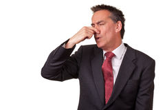 Business Man in Suit Smelling Something Bad. Middle Age Businessman in Suit Smelling Something Bad royalty free stock image
