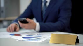 Business man in suit using phone, annual report on table, golden blank nameplate. Stock photo stock image