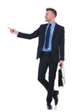 Business man with suitcase points to side Stock Images