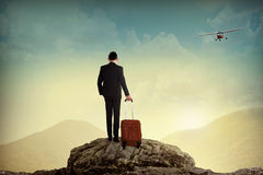 Business man with suitcase on the top of the mountain Royalty Free Stock Photo