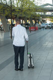 Business man with a suitcase waiting for a taxi at the airport Royalty Free Stock Image