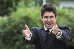 Business man in a suite, pointing at camera to y Stock Image