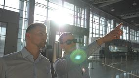 Business man in sunglasses pointing something to his colleague. Two young businessmen looking at flight schedule at. Airport. Bright sun shining through the stock video