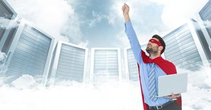 Business man superhero with laptop and hand in air against servers and clouds with white interface Stock Photos