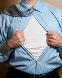 Business man superhero opens shirt. Close up detail of business man opening blue dress shirt. Blank white t-shirt underneath reveals secret identity or provides stock photos