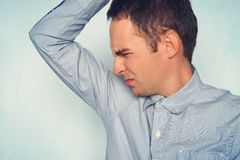 Business man with sweating under armpit in blue shirt. young guy sniffs his armpits and makes a displeased expression stock image
