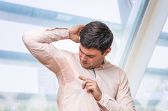 Business man with sweating under armpit in office. Business man with sweating under armpit in pink shirt Royalty Free Stock Photo