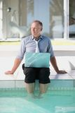 Business man at the swimming pool using a laptop Stock Photo
