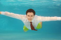 Business man swimming underwater in the pool. Wearing white shirt and red tie Stock Images