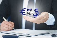 Euro to  Dollar conversion. Man in a dark suit (body and hands only) writing with pen in his right hand on a spiral bound pad  with Euro and Dollar symbols above stock image