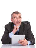 Business man with tablet looks away pensively Stock Photos