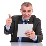 Business man with tablet shows the thumb up sign Royalty Free Stock Images