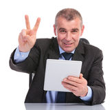 Business man with tablet shows the victory sign Stock Image