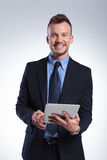 Business man with tablet smiles at you Stock Image