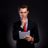 Business man with tablet thinking Stock Image