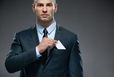 Business man takes out white card from the pocket Royalty Free Stock Photo