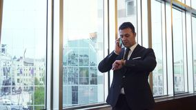 Business man takes a phone call and looks at his wrist watch royalty free stock photography