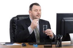 Business man takes pill sitting at the desk Royalty Free Stock Images