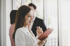 Business man taking note in front of two friend office worker in the background. for woman confidence concept. Business men is taking note in front of two friend royalty free stock image