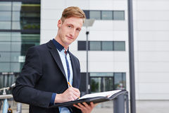Business man taking notes in files Royalty Free Stock Image
