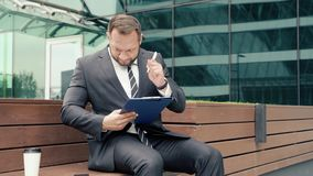Business man taking notes on paper outdoors.  stock footage