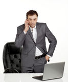 Business man talking. On a mobile phone in his office with a lap top in front of him Royalty Free Stock Images