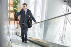 Business man talking on cell phone while on escalator Stock Photos