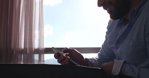 Business Man Talking On Cell Phone At Home. With sun flares coming from window Royalty Free Stock Photo