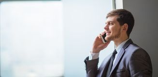 Business man talking on cell phone. Young business man talking on cell phone at modern office Royalty Free Stock Image