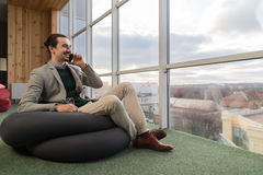 Business Man Talking Cell Smart Phone Call Sit in front Panoramic Window Businessman In Coworking Center Royalty Free Stock Photo