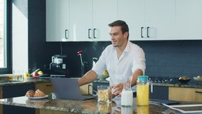 Business man talking at computer in kitchen. Closeup person having online chat. Business man talking at laptop computer in luxury kitchen. Closeup smiling male stock video