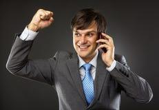 Business man talking on his cellphone. Enjoying success Royalty Free Stock Image