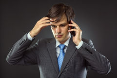 Business man talking on his cellphone. And thinking Stock Photography