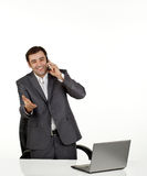 Business man talking on a mobile. Happy and pleased business man talking on a mobile phone in his office with a lap top in front of him Stock Image