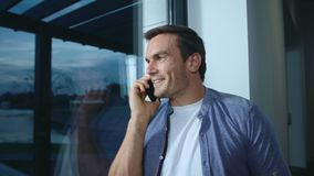 Business man talking mobile in luxury house. Relaxed man speaking cellphone. stock footage