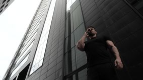 Business man talking on a mobile phone in the background of skyscrapers. . Business man talking on a mobile phone in the background of skyscrapers. The stock footage
