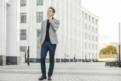 Business man talking by mobile phone next to modern business center. royalty free stock photos