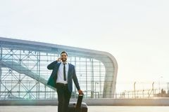 Business Man Talking On Mobile Phone Outdoors. Man With Suitcase Traveling On Business Trip. High Resolution Stock Photo