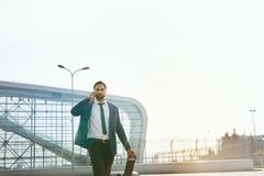 Business Man Talking On Mobile Phone Outdoors. Man With Suitcase Traveling On Business Trip. High Resolution Royalty Free Stock Photo