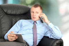 Business man talking on a mobile phone and working on his tablet. Lying on the  black leather sofa Stock Photo