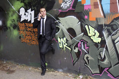 Business man talking on the phone. Young businessman talking on the phone in an urban area with graffitis on the walls royalty free stock images