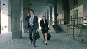 Business man talking on the phone and business woman walking with him pulling her suitcase. They are going to have an important meeting. Slow motion stock video footage