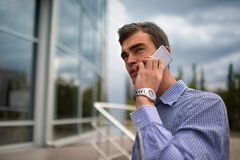 Business man talking on a phone. Handsome guy calling a phone on a blurred background. Conversation concept. Copy space. Stock Image